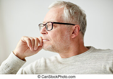 close up of senior man in glasses thinking - old age,...