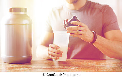 close up of man with protein shake bottle and jar - sport,...