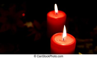 Burning candles - Closeup of burning red wax candles on dark...