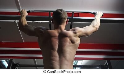 Strong man doing pull-ups in the gym