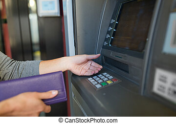 close up of hands withdrawing cash at atm machine - finance,...