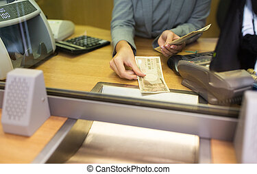 clerk counting cash money at bank office - people,...