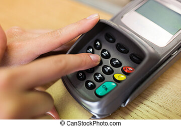 close up of hand entering code to money terminal - finance,...