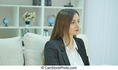 Relaxed businesswoman enjoying her coffee sitting on a sofa in her office