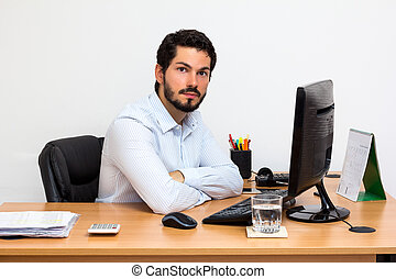 Young entrepeneur at his desk - Worker using dress shirt at...