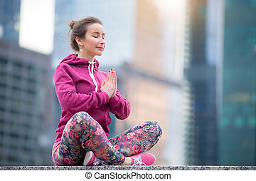 Young woman in Sukhasana pose against the city - Young happy...