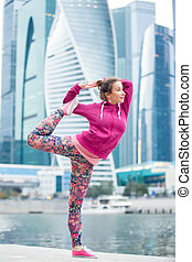 Young woman in Natarajasana pose against the skyscrapers -...