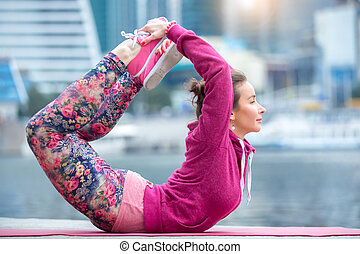 Young woman in Bow pose against river and city