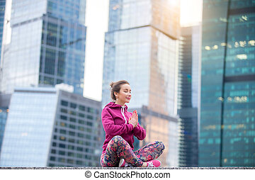 Young woman in Sukhasana pose against the skyscrapers -...