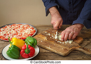 Man knife sliced onion pizza on a wooden board horizontal