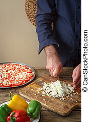 Man knife sliced onion pizza on a cutting board vertical