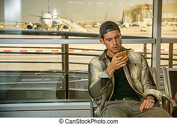 Young man at airport using cell phone - Portrait of a man in...