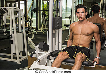 Shirtless young man working out on gym equipment
