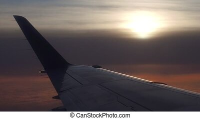 Edge of airliner wing against cloudy sunset. 4k aerial video...