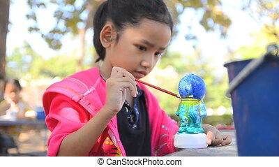 Close up shot asian little girl painting the doll