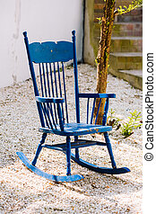 Blue antique rocking chairs on stone porch welcome visitors...