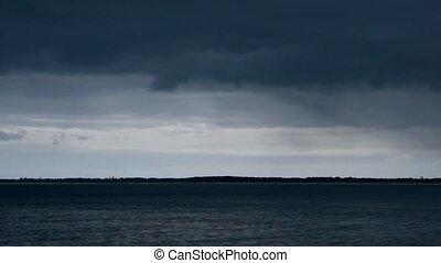 Dark rain clouds moving over lake or river on background of...