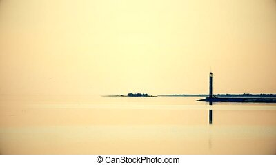 Seagull flies over sea with lighthouse reflected in calm...