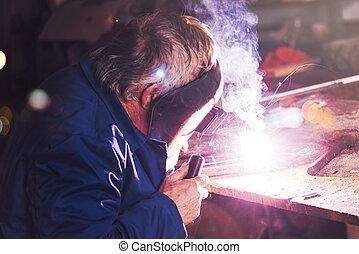 Welder welding in workshop - Mature welder welding two metal...