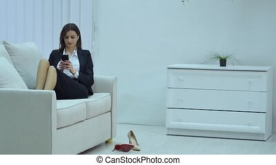 Charming beautiful business woman casual style using, chatting, connecting, social, calling and watching smartphone is sitting on sofa.