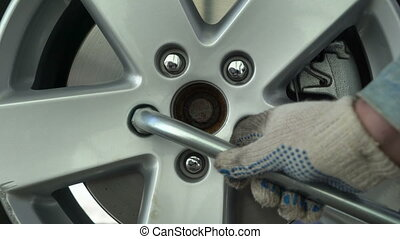 Changing tire on a car using wrench to tighten wheel nuts