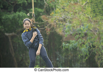 asian teen age hanging on safety rope in outdoor adventure...