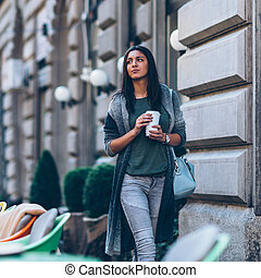 Woman with take-away coffee in the city