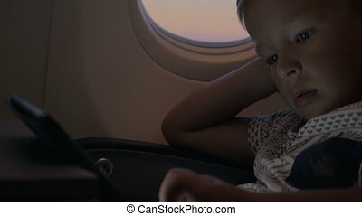 Child using tablet PC in airplane - Boy traveling by plane...