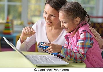 Mother and daughter play videogame - Happy mother and...
