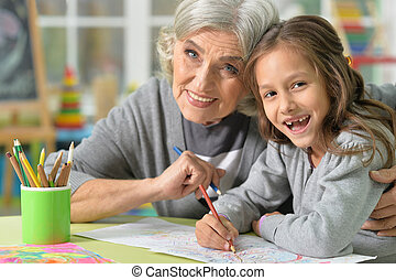 Grandmother and granddaughter drawing - Portrait of...