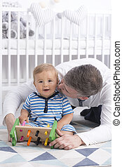 Dad kissing small smiling baby - Carring dad kissing with...