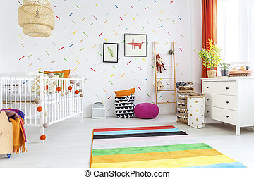 White baby room with cot and colorful rug