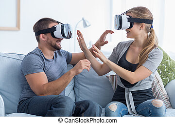 Happy couple wearing VR goggles - Shot of a happy young...