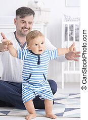 Baby making first steps with father - View of baby making...