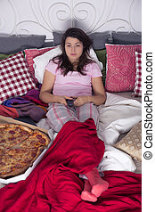 Single woman eating pizza - Single woman lying in bed,...