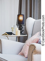 Room with armchair, book and lamp standing on side table