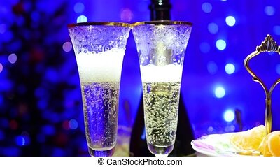 Sparkling wine is poured into glasses. In the background, bokeh lights.