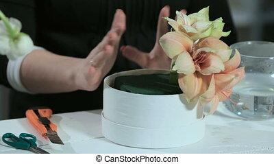 Florist show a flower arrangement in the round form white box