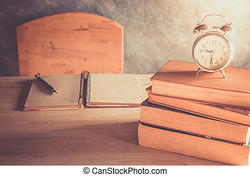 book - Alarm clock on stack books with open notebook on...