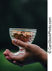 Close Up Of Woman Holding glass bowl with Almonds nuts.
