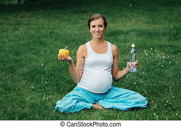 pregnant yoga woman with a bottle of water and bell pepper, in the lotus position. park ,grass . outdoor, forest.