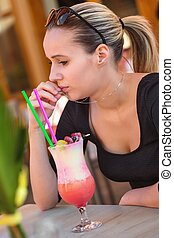 Portrait of young brunette beauty with a drink on the table...
