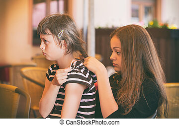 The girl combs her hair to her friend - Two young girls...