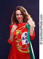Beautiful brunette woman with Flag of Portugal. Toned image.