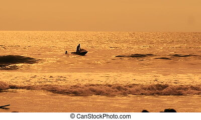 Jet ski rides on the sea waves at sunset. Two men actively...