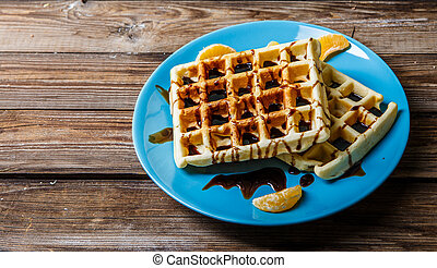 Viennese waffles on blue plate on wooden table with...