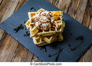 Viennese waffles with chocolate, mandarine and ice-cream on...