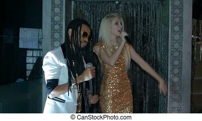 Duet African American man and a blonde woman singing. Slow...
