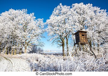 Wooden hunting hideout in front of trees covered by frost -...