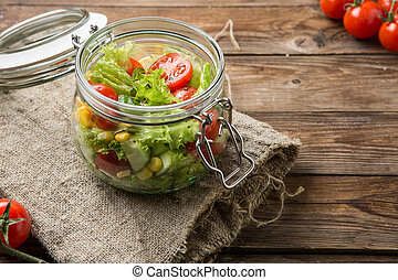 Traditional vegetable salad with corn in jar on table with...